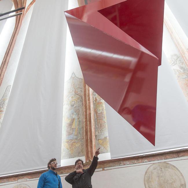 Der Ausstellungsgestalter begutachtet eines der Gestaltungselemente in der Pfalzkapelle St. Ulrich. © Uwe Moosburger (altrofoto)